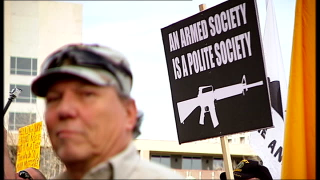 texas has some of the most lax gun regulations man pull focus ' an armed society is a polite society' placard 'come and take it' placard with hello... - pink shirt stock videos and b-roll footage