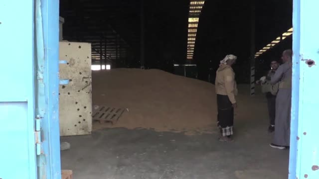 gunshots reverberate through a battle scarred granary in the port city of hodeida where a mountain of grain meant for starving yemenis remains... - granary stock videos & royalty-free footage