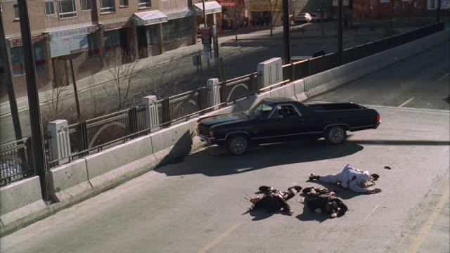 ws ha gunshots riddling car, car explodes and burns, three people lying on asphalt - stunt stock videos & royalty-free footage
