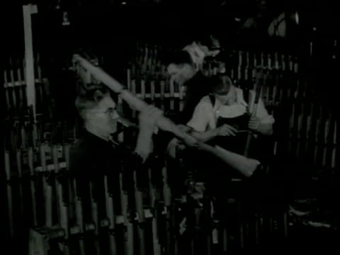gunsmiths examining rifle guns racks of rifles ms woman in factory working w/ ammunition cartridges turning slowly on machine vs women working w/... - ammunition stock videos & royalty-free footage