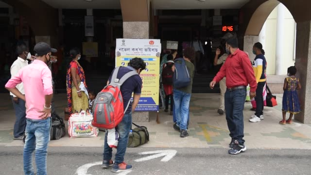 guwahati, assam, india. 10 june 2020. passengers along with their luggage stand in a queue outside guwahati railway station to board a train, during... - lavoratore emigrante video stock e b–roll