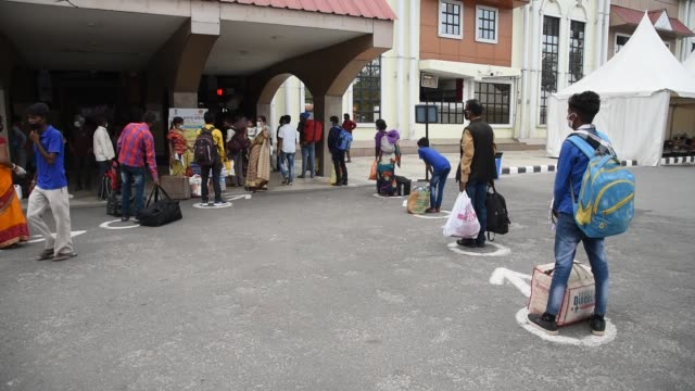 guwahati assam india 10 june 2020 passengers along with their luggage stand in a queue outside guwahati railway station to board a train during the... - protection stock videos & royalty-free footage
