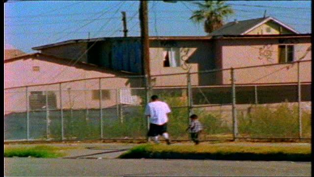 guy and boy walking down street together in los angeles, california - 男児のみ点の映像素材/bロール