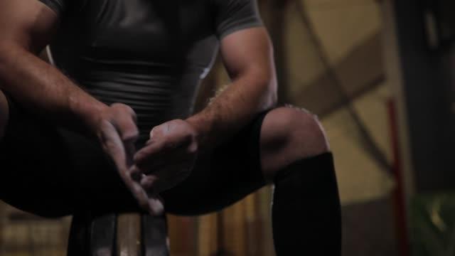 vídeos de stock, filmes e b-roll de cara aplicando esportes giz nas mãos antes de halterofilismo - giz equipamento esportivo