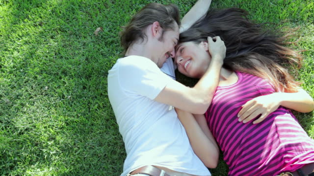 ms guy being lie down with girl on the grass / los angeles, california, united states - sdraiato video stock e b–roll