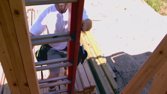 stockvideo's en b-roll-footage met guy climbing a ladder - ladder gefabriceerd object