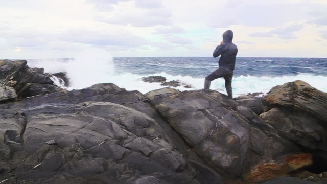 guy contemplating and taking pictures of the big waves during a windy day in the north coast of menorca island. - ein mann allein stock-videos und b-roll-filmmaterial