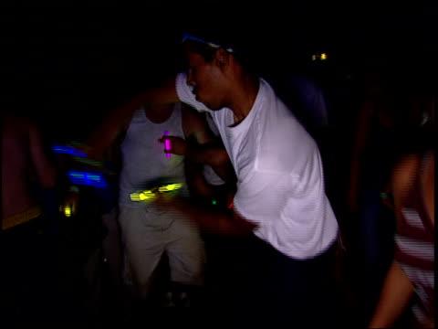 vidéos et rushes de guy dancing with glowsticks at a rave - sortir en boîte de nuit
