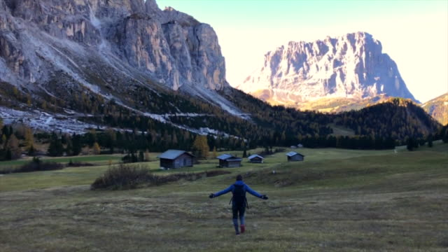 Guy discovering the beautiful Dolomites mountains with meadows and alpine houses.