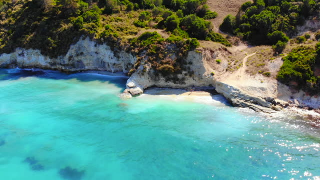 vídeos de stock e filmes b-roll de guy doing a boomerang drone selfie in idyllic beach with turquoise colors in greek island. - bumerangue