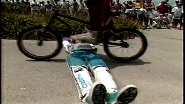 guy doing bmx tricks and jumps over guy on the ground front of crowd - bmx cycling stock videos and b-roll footage