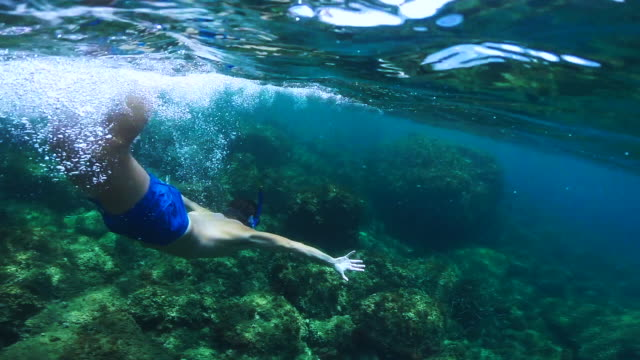 guy doing snorkel exploring the medes islands in the shoreline of costa brava mediterranean sea during summer vacations in a paradise place recorded with dome and underwater view. - badeshorts stock-videos und b-roll-filmmaterial