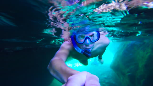 guy doing snorkel exploring the natural cave in the shoreline of costa brava mediterranean sea during summer vacations in a paradise place recorded with dome and underwater view. - badeshorts stock-videos und b-roll-filmmaterial