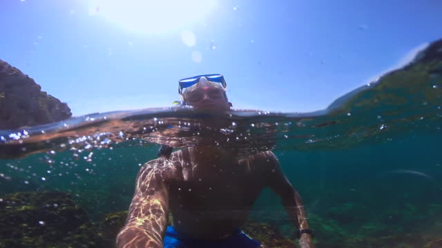 guy doing snorkel recording himself exploring the medes islands in the shoreline of costa brava mediterranean sea during summer vacations in a paradise place recorded with dome and underwater view. - サーフパンツ点の映像素材/bロール