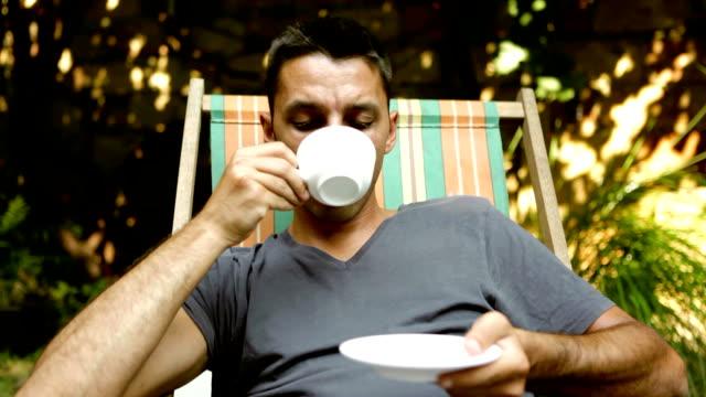 vídeos de stock e filmes b-roll de homem beber café em seu jardim - bebida quente