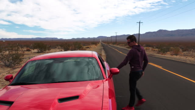 vidéos et rushes de guy driving a american car in a straight road at the california desert during road trip. - route 66
