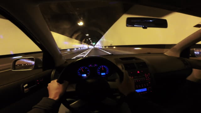 Guy driving from personal perspective holding steering wheel inside tunnel at night during trip with nice straight road and vanishing point.