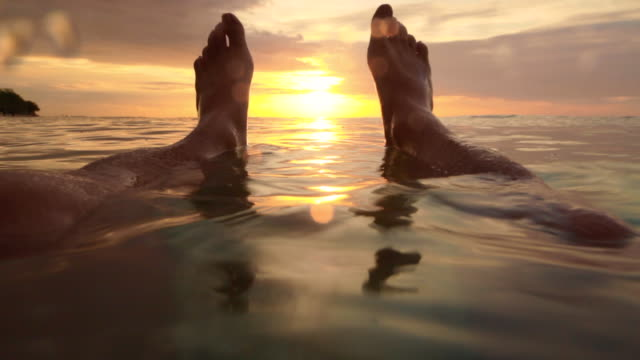 vidéos et rushes de guy during travel vacations floating on water contemplating the sunset from personal perspective with his legs in the frame with nice colors and calm water. - personal perspective