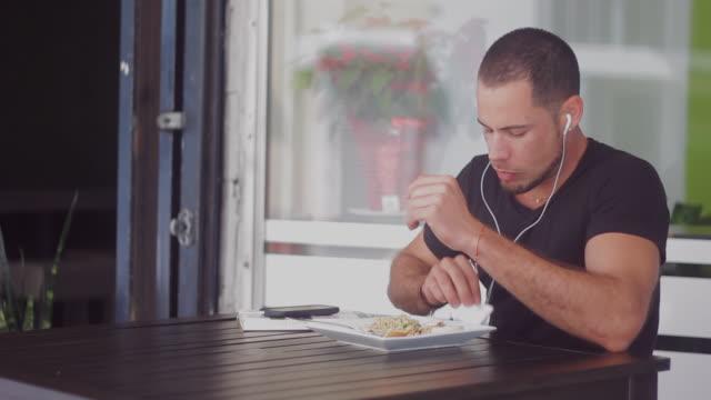guy eating and listening to music - ziegenbart stock-videos und b-roll-filmmaterial
