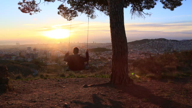 guy enjoying sunrise over barcelona city from cool viewpoint with unique perspective of the city, sitting on swing relaxing and contemplating the view from lonely tree in the collserola mountains. - rope swing stock videos & royalty-free footage