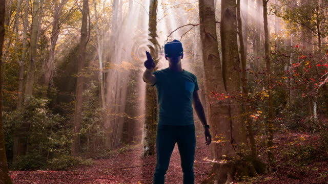 guy experiencing the virtual reality headsets immerse in another dimension touching and feeling the trees dimension scenario transported in a beautiful nature forest. - virtuelle realität stock-videos und b-roll-filmmaterial