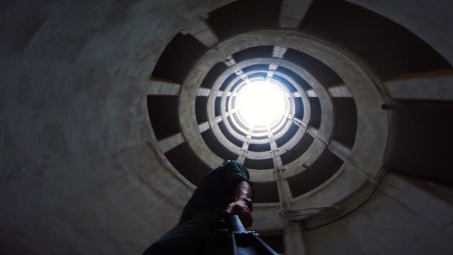 Guy exploring the urban corners of the Barcelona city, under a huge spiral ramp in a decay parking from directly below view and nice vanishing point.