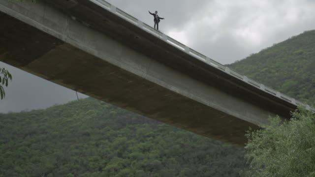 vídeos y material grabado en eventos de stock de guy falling from a bridge with a special harness - puenting