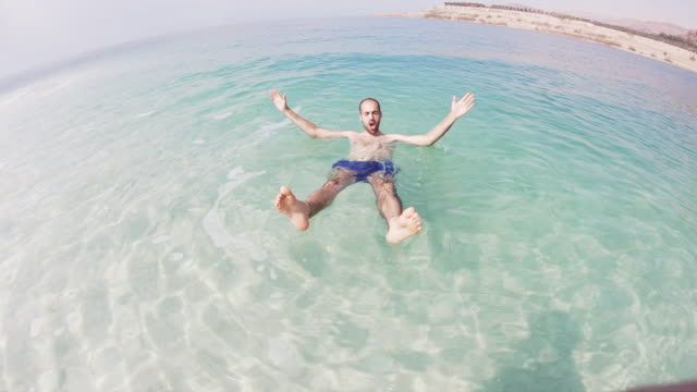 vidéos et rushes de guy floating in the dead sea during vacations. - paysage marin