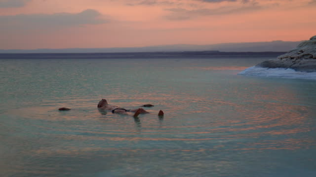 guy floating in the dead sea during vacations with sunset light. - 水に浮かぶ点の映像素材/bロール