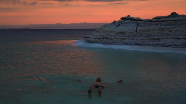 guy floating in the dead sea during vacations with sunset light. - standing water stock videos & royalty-free footage