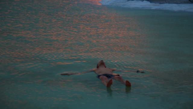 Guy floating in the Dead Sea during vacations with sunset light.