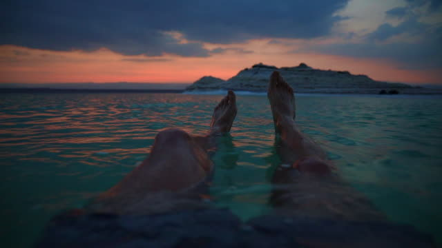 vídeos de stock e filmes b-roll de guy floating in the dead sea during vacations with sunset light. - ponto de vista