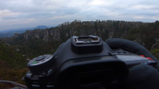 Guy from personal perspective contemplating the view in the cliff edge taken pictures with the photography camera in the beautiful Saxon National Park in Germany with stunning views of the rock formations and Saxon landscape mountains.