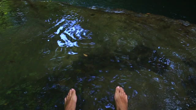 guy from personal perspective cooling off in nice natural pools in the river with legs during hot summer days in the catalonia region. - parte de una serie video stock e b–roll
