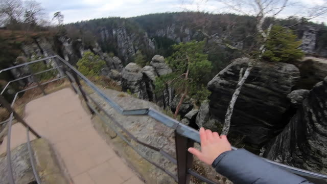 Guy from personal perspective doing hiking in the beautiful National Park in Germany with stunning views of the rock formations with vertigo and adrenaline sensations.