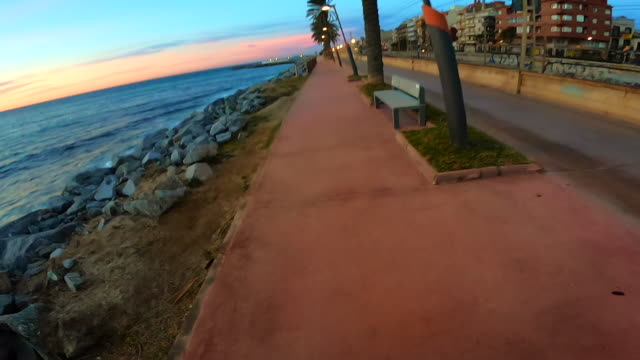 vidéos et rushes de guy from personal perspective doing sport in sunrise with longboard skating in the city boardwalk. - personal perspective