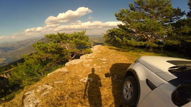 Guy from personal perspective driving car on top of cliff descending and contemplates the view in the Catalan Pyrenees during a summer trip.