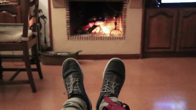 Guy from personal perspective getting cosy at countryside house in front of fireplace in winter covered with blanket in a relaxing Christmas vacations.