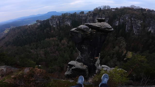 guy from personal perspective sitting in the cliff edge with pillar rock formation in front in the beautiful saxon national park in germany with stunning views of the rock formations with vertigo and adrenaline sensation. - 手足点の映像素材/bロール