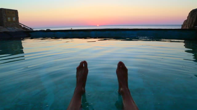 guy from personal perspective swimming in a natural pool in the mediterranean sea costa brava recording his feet with the sunrise on the background in a stunning outdoor with great colors. - utebassäng bildbanksvideor och videomaterial från bakom kulisserna