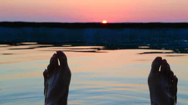 Guy from personal perspective swimming in a natural pool in the Mediterranean Sea Costa Brava recording his feet with the sunrise on the background in a stunning outdoor with great colors.