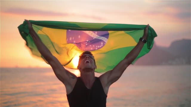 guy holds brazilian flag in the air and cheers on ipanema beach at sunset - superare le avversità video stock e b–roll