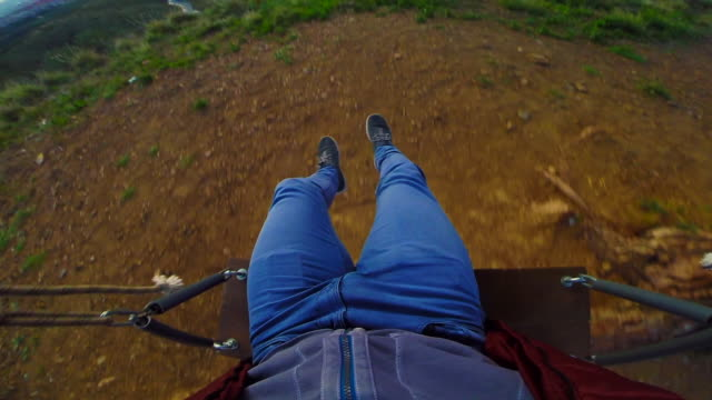 Guy in slow motion from personal perspective enjoying sunrise over Barcelona city using action cam from cool viewpoint with unique perspective of the city, sitting on swing relaxing and contemplating the view from lonely tree in the Collserola mountains.