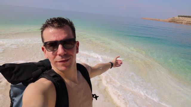 guy in the dead sea during vacations. - galleggiare sull'acqua video stock e b–roll