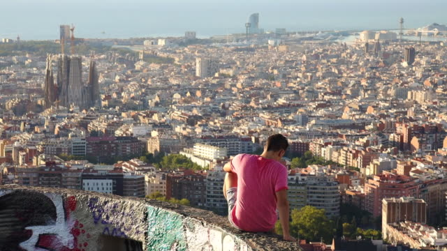 guy in the military bunkers viewpoint over barcelona city during sunrise. - 防空壕点の映像素材/bロール