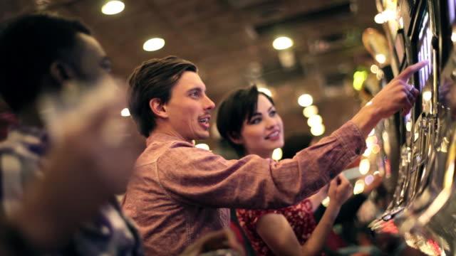 vídeos y material grabado en eventos de stock de guy learns how to play slots with friends in las vegas casino - máquina con ranura