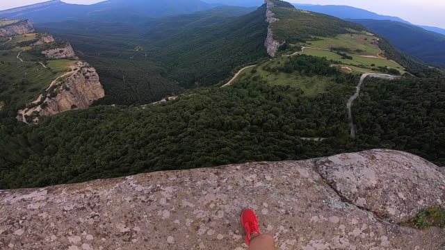 guy on a stunning viewpoint with nice green canyon formation. - 高い点の映像素材/bロール