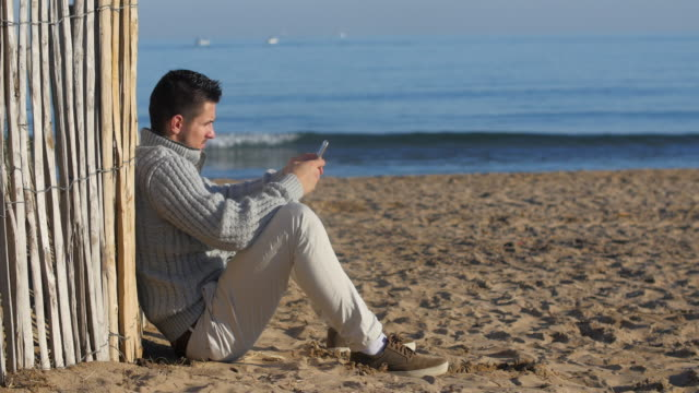 guy on his phone at the beach.