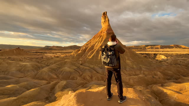 guy photographing the sandstone formations in the bardenas reales badlands in spain. fotografiando el cabezo de castildetierra en el paisaje desertico de las bardenas reales en el norte de españa. - national landmark stock videos & royalty-free footage