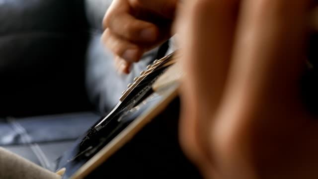 Guy spelen van akkoorden op een zwarte akoestische gitaar